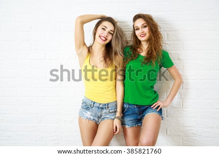 Two Sexy Smiling Hipster Girls at White Wall