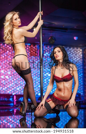 Two sexy striptease dancers posing on stage. While dancing on pole in erotic underwear  - stock photo