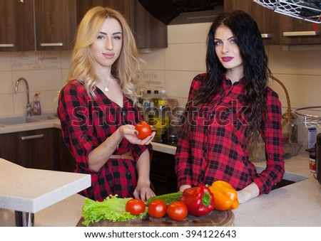 Two sexy woman blond and brunette in red shirt cooking on kitchen. Blurred background.