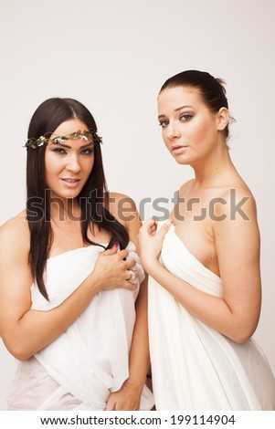 Two sexy women covered with transparent textile on white isolated background