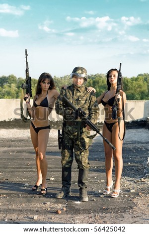 Two sexy women in underclothes leaning on soldier`s shoulders