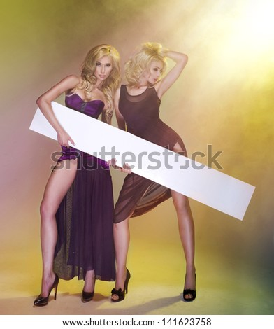 Two sexy young women in dress with board - stock photo