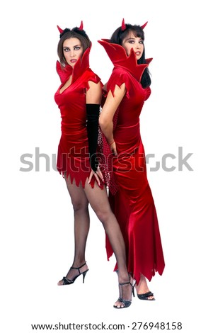 Two Sexy Young Women in Halloween costumes of Devils Standing at the White Background - stock photo