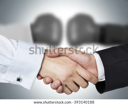 Two shaking hands, two blurred hands in boxer gloves at background. Concept of double game.