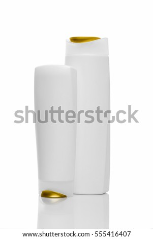 Two Shampoo bottles on white background. Gold and white bottles.