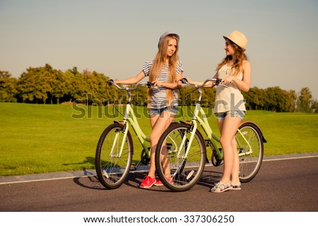 Two shapely girls together   walking with a bicycle - stock photo