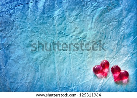 Two shining hearts over blue wrapping paper background - stock photo