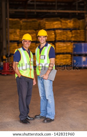 two shipping and warehouse worker portrait in workplace - stock photo