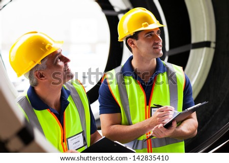 two shipping company employees inspecting tires after importing - stock photo