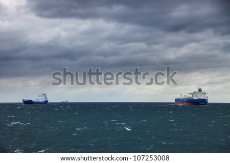 Two ships at sea and the upcoming storm. - stock photo