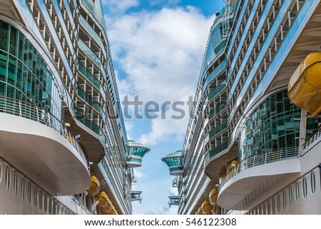 Two Ships Passing at the Docks with blue cloudy sky between