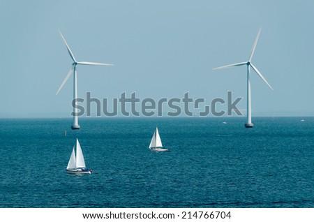 Two ships sailing near to marine windmills in copenhagen. Denmark - stock photo