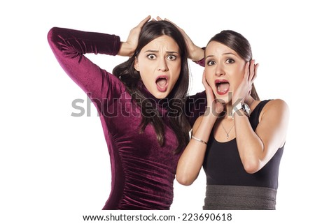 Two shocked young woman on white background - stock photo