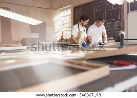 Two shop owners working on frame designs in their workshop - stock photo