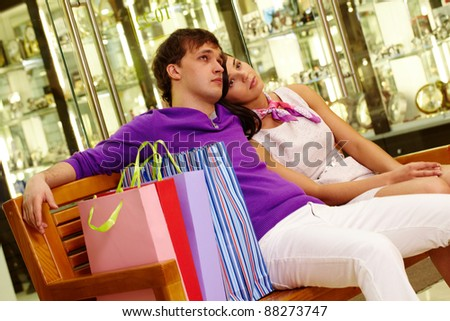 Two shopaholics having rest after good shopping in the mall - stock photo