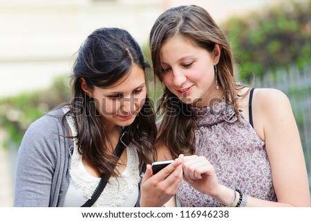 Two shopping girls in park with a mobile phone, italy - stock photo