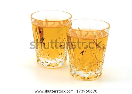 Two shot glasses of whiskey against a white background - stock photo