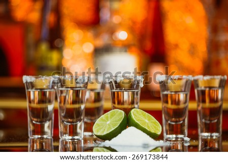 two shots of tequila with lime and salt on a  wooden table bar on the background of bright lights of the bar - stock photo