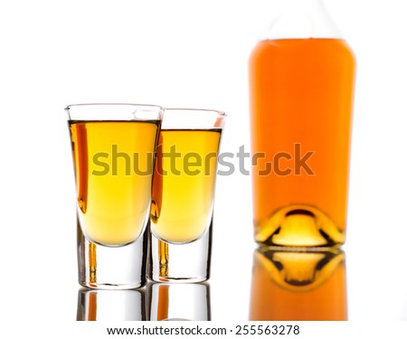 Two shots of whisky and bottle on a white - stock photo
