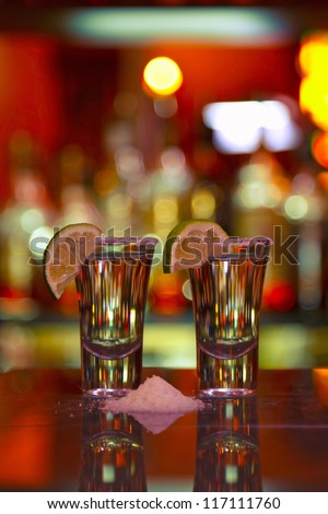 two shots tequila with lime and salt on wooden table bar, background bright lights