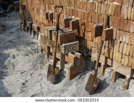 Two shovels against bricks wall, bricklayer - stock photo