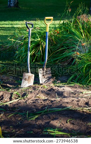 Two shovels in ground - stock photo