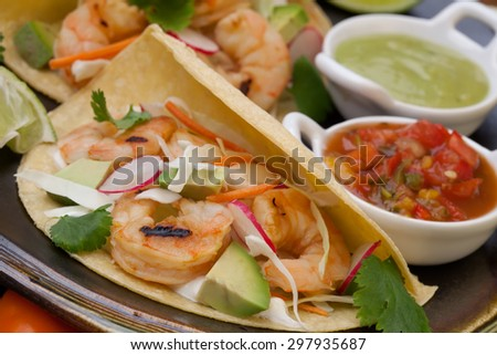 Two shrimp tacos with salsa, guacamole, beer, garnished with mini bell pepper and lime.