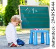 Two sibling boys at blackboard practicing mathematics, outdoor school or nursery. Kid learning and schoolboy concept. On summer sunny day. Back to school. - stock photo