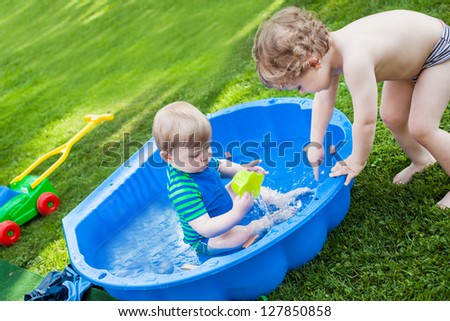 Two sibling boys with water in summer garden on sunny day - stock photo