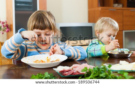 Two  siblings eating food together at wooden table - stock photo