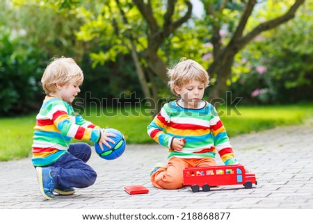 Two siblings, kid boys in colorful clothing with stripes playing with red school bus and toys in summer garden on warm sunny day. Learning to play and communicate together.