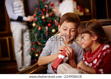 Two siblings opening Christmas gift with their parents decorating fir-tree on background - stock photo