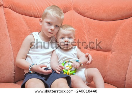 Two siblings sitting on the coach and looking straight at the camera. - stock photo