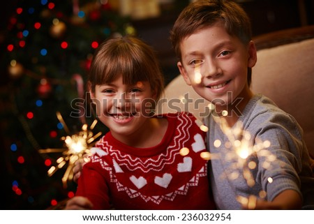 Two siblings with Bengal lights celebrating Christmas