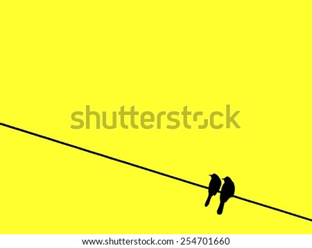Two silhouette birds perching on wire on yellow background