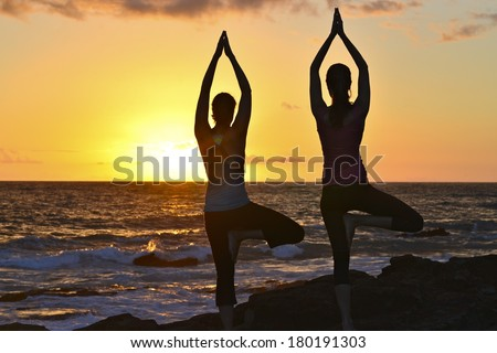 two silhouette figures doing standing yoga stock photo