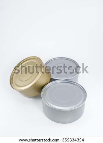 Two silver and one gold can of tuna with no label against a white background.