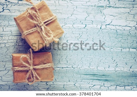 two simple gift box in wrapping paper on the old table - stock photo