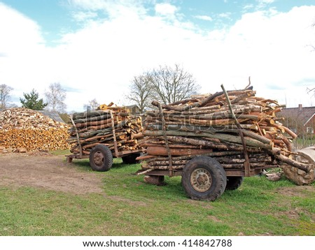 Two simple tractor trailers with stacked firewood logs.