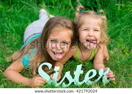 two sister girls lying on meadow green grass like friends playing - stock photo