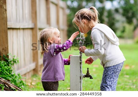 Two sisters- a little toddler girl and her older sister drinking water from the tap outside in the park in summer - stock photo
