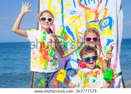 Two sisters and brother playing with paint on the beach at the day time. Concept Brother And Sister Together Forever - stock photo