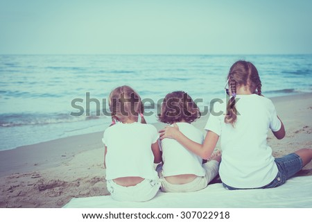 two sisters and brother sitting on the beach at the daytime - stock photo
