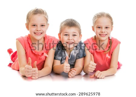 Two sisters and little brother lying on the floor , three children - isolated on white background - stock photo
