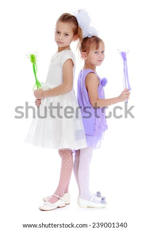 Two sisters are each other back and holding a magic wand.Studio photo, isolated on white background. - stock photo
