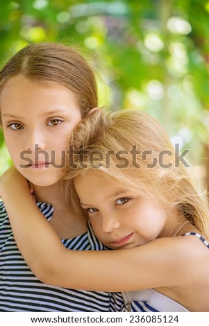 Two sisters are smiling on background of summer green park. - stock photo