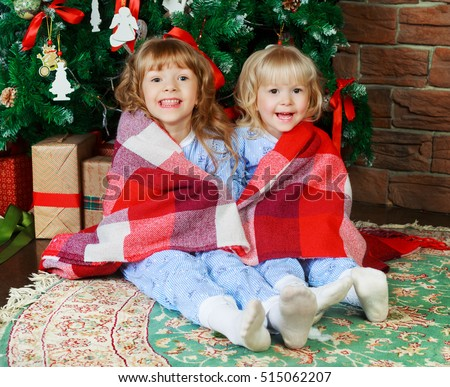 two sisters at home with a Christmas tree