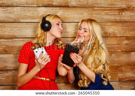 Two sisters, blonde, listening to music on headphones. One girl sends an air kiss another. Girls are holding a smartphone and a tablet pc. Sisters sitting in the bedroom. - stock photo