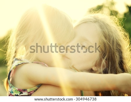 Two sisters Cuddled up together. Back lighting sunlight. MANY OTHER PHOTOS FROM THIS SERIES IN MY PORTFOLIO. - stock photo