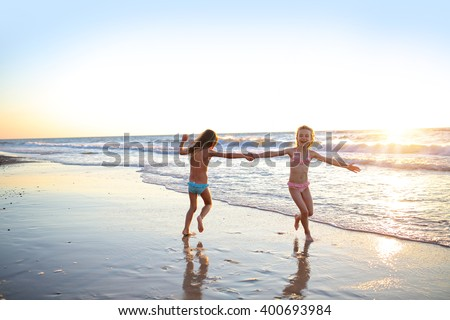 Two sisters dancing on the beach at sunset - stock photo